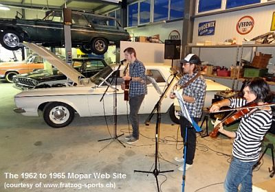 Band partying  with 1962 Plymouth in shop